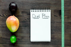 Tasty food for slimming. Notebook for diet plan and fruits on wooden table top view mock up Royalty Free Stock Images