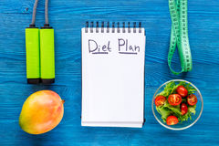 Tasty food for slimming. Notebook for diet plan, salad, fruits and measuring tape on blue table top view mock up Royalty Free Stock Images