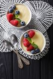 Tasty food: vanilla pudding with raspberries and blueberries clo. Se-up on the table. Vertical top view from above Royalty Free Stock Photos