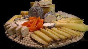 Tasty French cheeses on a plate on a black background. Circular movement of the camera around of pieces tasty French cheeses on a plate on a black background stock video footage