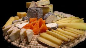 Tasty French cheeses on a plate on a black background. Circular movement of the camera around of pieces tasty French cheeses on a plate on a black background stock footage