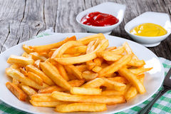 Tasty french fries on plate, on wooden table background Stock Photography