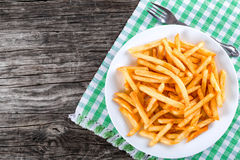 Tasty french fries on plate, on wooden table background Stock Image