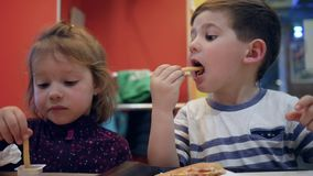 Tasty French fries with sauce for little girl and boy, Male child chews hamburger, Fun kids play with meal in fast food stock video