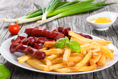 Tasty french fries and sausages on plate, close-up Royalty Free Stock Images