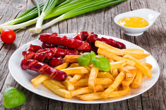 Tasty french fries and sausages on plate, close-up Royalty Free Stock Photography