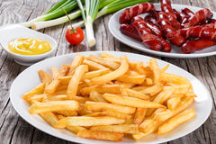 Tasty french fries and sausages on plates, close-up Stock Images