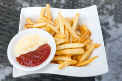 Tasty french fries in  white plates on glass table background Royalty Free Stock Image