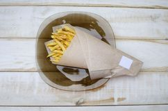 Tasty french fry on the paper bag on the white wooden table. Hi royalty free stock photography