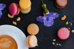 Tasty French macaroons on black stone background. Amazing morning with a cup of coffee and good mood. Tasty French macaroons on a black stone background Royalty Free Stock Photos
