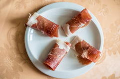 Tasty fresh bacon in white plate. On the table Royalty Free Stock Photography