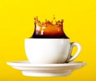 Tasty fresh black coffee in cup splash crown on yellow vibrant b. Ackground. Art Design Creativity Idea Royalty Free Stock Image