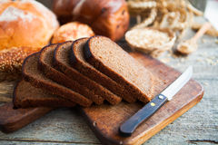 Tasty fresh bread and wheat on the old wooden table Royalty Free Stock Image