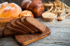 Tasty fresh bread and wheat on the old wooden table Stock Photos