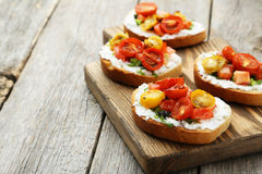 Tasty fresh bruschetta. With tomatoes on cutting board on grey wooden background royalty free stock photos