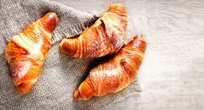 Tasty fresh croissants on a bright  wooden background. Top view Royalty Free Stock Images