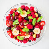 Tasty fresh fruit salad in glass plate on white wooden background. Flat lay. Top view. Royalty Free Stock Images
