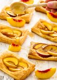 Tasty fresh homemade puff pastry with peach and honey on the whi Stock Photography