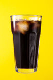 Tasty fresh iced cold black coffee with ice on yellow vivid back Royalty Free Stock Photos