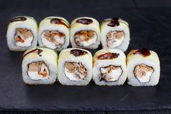 Tasty fresh maki sushi roll with eel and unagi sauce, covered wi Stock Photography