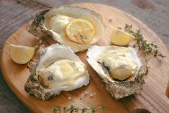 Tasty fresh oysters with sliced lemon on cutting board. Aphrodisiac food for increasing sexual desire.  stock photo