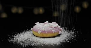 Tasty fresh donut lay on black surface and gets sprinkle with icing sugar powder stock footage