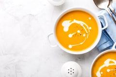 Pumpkin creamy soup decorated with fresh cream stock photos