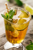 Tasty fresh refreshing summer tea drink with ice, cold tea, lime. And mint in glass on wooden background. Closeup Royalty Free Stock Photo