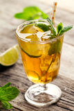 Tasty fresh refreshing summer tea drink with ice, cold tea, lime. And mint in glass on wooden background. Closeup Stock Image