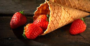 Tasty fresh ripe red strawberries in a cornet. Or waffle ice cream cone spilling onto a rustic wood counter in banner format Royalty Free Stock Photos