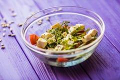 Tasty fresh salad on purple wooden table. Food Royalty Free Stock Image