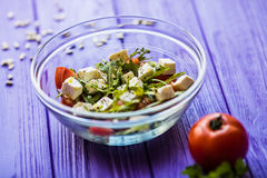 Tasty fresh salad and tomate on purple wooden table. Food Stock Photography