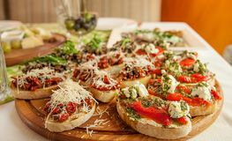 Tasty fresh sandwiches. Italian sandwiches with paprika, cheese, tomatoes and pesto sauce on a wooden plate. royalty free stock photos