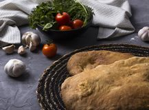 Tasty fresh tandoori bread on gray table with tomato, garlic and parsley. National georgian cuisine and food. Top view or flat lay royalty free stock image