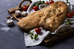 Tasty fresh tandoori bread on wooden tray with tomato, garlic and parsley. National georgian cuisine and food. Copy space for text. Top view or flat lay royalty free stock photography