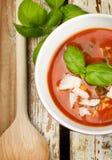 Tasty fresh tomato soup and basil. Tasty fresh tomato soup , basil on wooden background Stock Photos