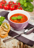 Tasty fresh tomato soup basil and bread. On wooden background Royalty Free Stock Image