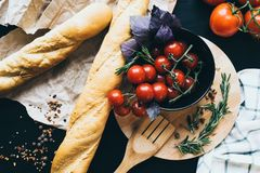 Tasty fresh tomatoes in a stylis black dish with delicious bread lying on wooden cutting board ready for cooking and Royalty Free Stock Photography