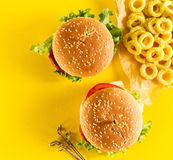 Tasty fresh unhealthy hamburgers with ketchup and vegetables and Royalty Free Stock Photo