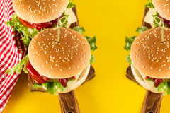 Tasty fresh unhealthy hamburgers with ketchup and vegetables on Royalty Free Stock Photography