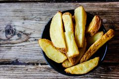 Tasty freshly home made fried potato wedges in a black plate stock photo