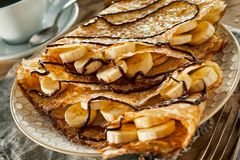 Tasty fried batter crepes with fresh bananas royalty free stock image