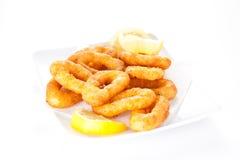 Tasty fried calamari. Plate of tasty fried calamari with lemon Stock Photos