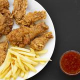 Tasty fried chicken drumsticks, spicy wings, French fries, chicken strips on a white plate over black background, top view. Close-. Up stock image