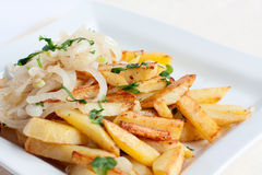 Tasty fried potatoes with onions. Tasty fried potatoes with onion rings on a white plate Royalty Free Stock Photos