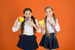 They are tasty. Fruits are high in vitamin. Cute schoolgirls like apples. School children with healthy apple snack. Little girls taking school snack break royalty free stock images