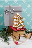 Gingerbread Christmas tree and gift on wooden sledge on a blue background. Tasty gingerbread Christmas tree and gift on wooden sledge on a blue background Royalty Free Stock Images