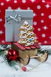Gingerbread Christmas tree and gift on wooden sledge. Tasty gingerbread Christmas tree and gift on wooden sledge Royalty Free Stock Photography