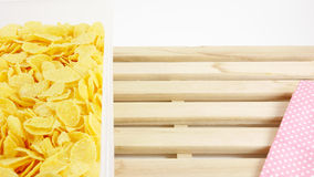 Tasty golden corn flakes in plastic container box on wooden tray Royalty Free Stock Photos