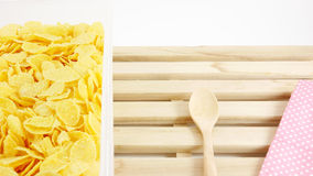 Tasty golden corn flakes in plastic container box on wooden tray Royalty Free Stock Photography